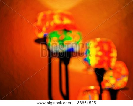 Un-focused blurry glasses for candles in romantic atmosphere shimmering yellow orange red, producing very warm light in front of a wall.