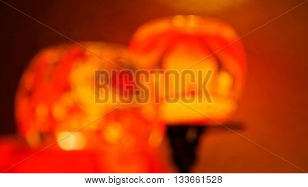 Closeup of blurred unfocused candle glasses in romantic atmosphere shimmering yellow orange red, producing very warm light in front of a wall.