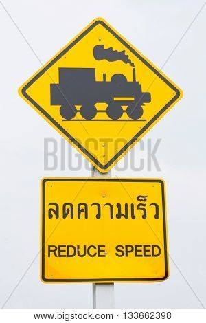 Kanchanaburi, Thailand, 30th April 2016. Isolated Street Sign 'Railroad Crossing' with Second Sign 'Reduce Speed' in Thai and English Language. Black historic locomotive on yellow rhombus.