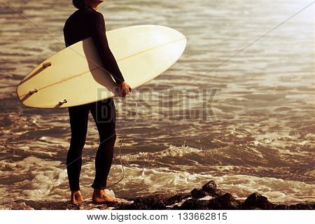 Surfer entering the ocean at sunrise.Ready for a great surfing day