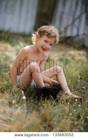 The kid plays with a puppy. On the ground covered with dry grass sits a little boy. He plays with a tiny black puppy. The boy looks into the camera and smiling.