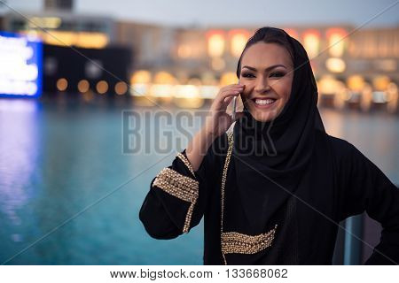 Attractive young arabic woman talking on a mobile phone in the city.
