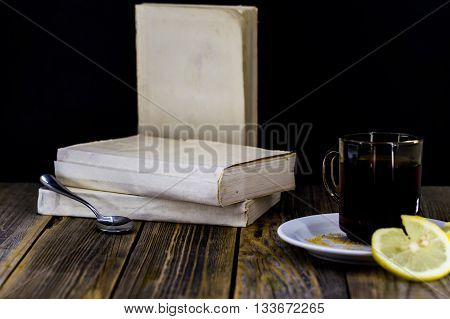tea Cup with lemon on a wooden background with books