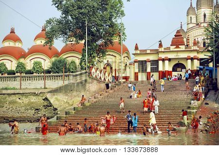 KOLKATA, INDIA - JAN 17, 2016: Many people bathing in water of river past historical Kali temple in area Dakshineswar on January 17, 2016. The beautiful temple was built in Bengal architecture style in 1855