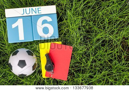June 16th. Image of june 16 wooden color calendar on green grass background with football outfit. Summer day.