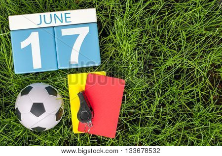 June 17th. Image of june 17 wooden color calendar on green grass background with football outfit. Summer day.