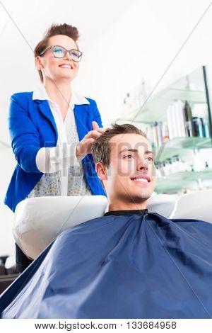 Female coiffeur washing men hair in hairdresser shop