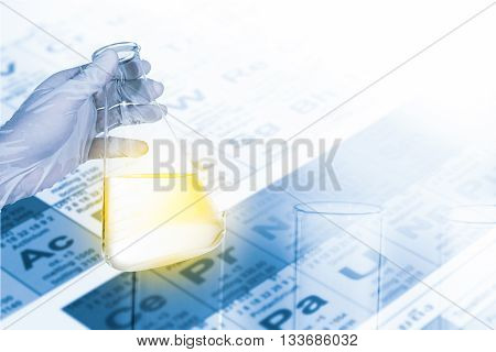 scientist holding flask for chemical test in chemistry lab test tube and periodic Table background