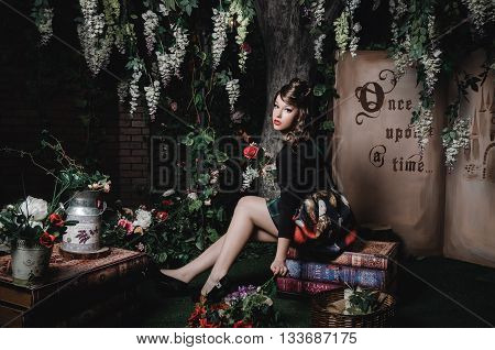 Magic portrait of romantic beautiful girl with wavy hair, red lips, art dress, holding rose flower, sitting on books. Fashion fairy tale about princess, walking mistery forest. Creative concept Once upon a tim