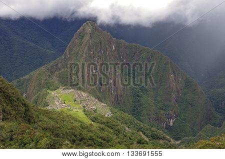 View of the Lost Incan City of Machu Picchu and Huayna Picchu mountain from Machu Picchu mountain .Low clouds .Cusco RegionSacred Valley Peru