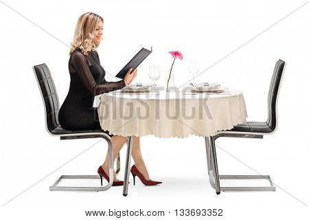 Young woman sitting at a restaurant table and looking at the menu isolated on white background