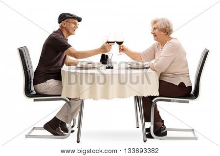 Elderly couple making a toast with red wine seated on a romantic rendezvous isolated on white background