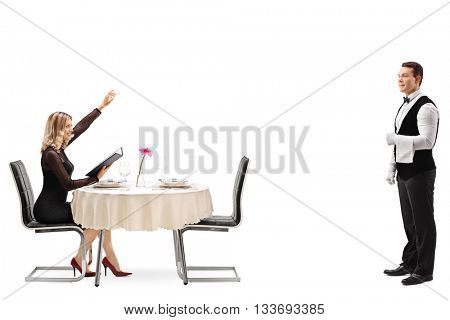 Blond woman sitting at a restaurant table and calling the waiter isolated on white background