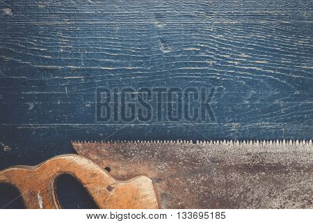 old rusty saw on the blue wooden background
