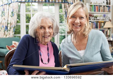 Senior Woman Looks At Photo Album With Mature Female Neighbor