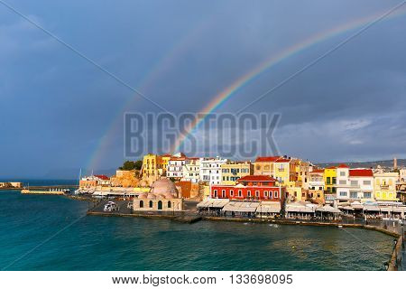 Double rainbow in a cloudy sky above old harbour of Chania with Venetian quay and Kucuk Hasan Pasha Mosque in summer day, Crete, Greece poster