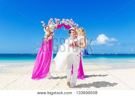 Wedding ceremony on a tropical beach in purple. Happy groom and bride under the arch decorated with flowers on the tropical sand beach. Wedding and honeymoon concept.