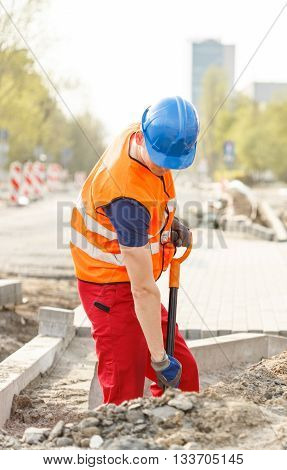 Workman in high-visibility vest using a shovel