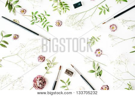 Workspace with paint brushes and rose buds. Flat lay overhead view. Artist working place