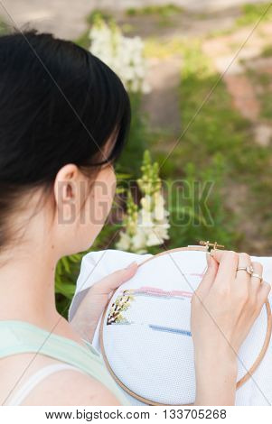 Young girl embroiders a pattern on the white material sweetie brunette engaged in needlework