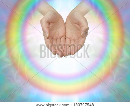 Rainbow healing circle - female cupped hands surrounded by a transparent circular rainbow with an inner white light on a soft colored background with copy space