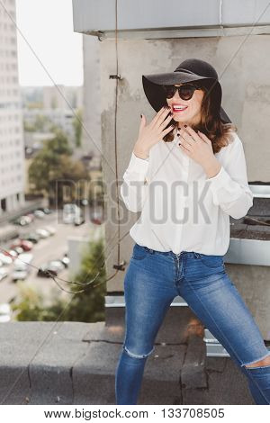 Young smiled woman is posing unaffectedly on a rooftop