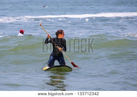 Young Woman Paddling On A Board In Punta Hermosa, Peru