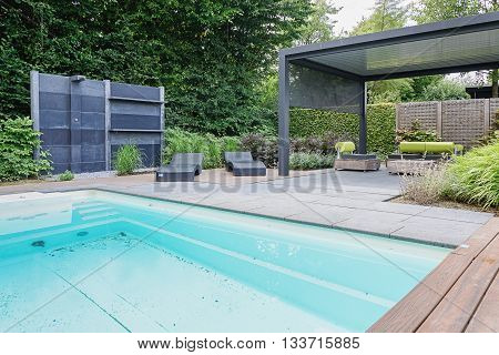 Appeltern The Netherlands July 22 2015: The Gardens of Appeltern is the inspiration garden park in the Netherlands. In this picture a swimmingpool with outdoors shower trendy sunloungers and overhang with trendy garden chairs.