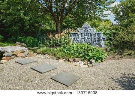 Appeltern, The Netherlands - July 22, 2015: The Gardens of Appeltern is the inspiration garden park in the Netherlands. In this picture a garden with a Buddhist scene in stone.