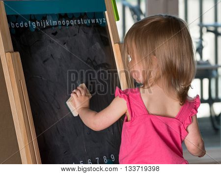 Young Baby Girl Cleaning A Blackboard