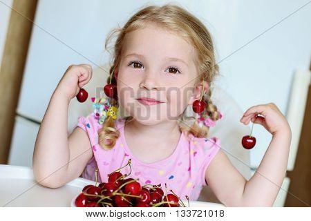 cute little girl eating cherries on white background