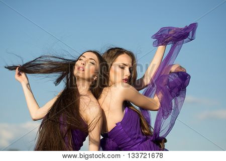 young pretty women with long windy hair in elegant violet dresses sunny day outdoor on blue sky background