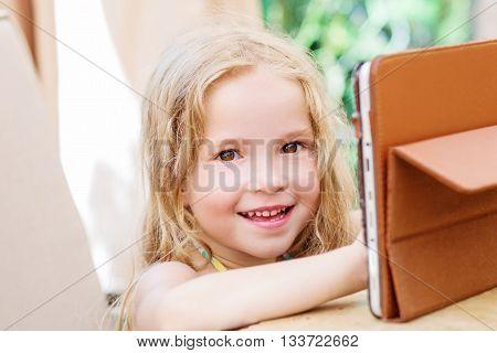 Happy little girl using tablet computer oudoors