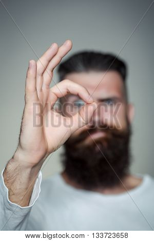 handsome young man with long beard and moustache on face with okey gesture of finger on grey background in studio