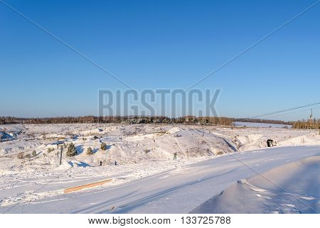Orel, Russia - January 10, 2016: People skiing on snow-covered hill near the ski lift.