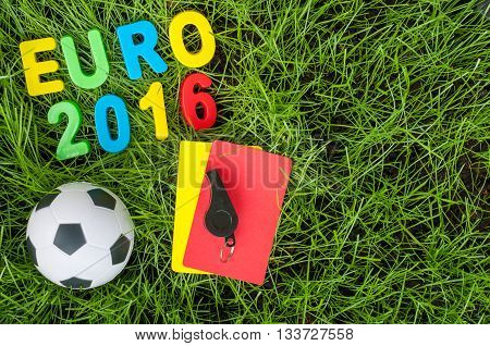 Euro 2016 football championship - image with ball, referee yellow, red card on green lawn. Symbol of soccer and fair play. Empty space for text.