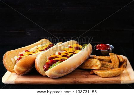 Two Hot Dogs Fully Loaded With Toppings And Potato Wedges On Wooden Board With Dark Background