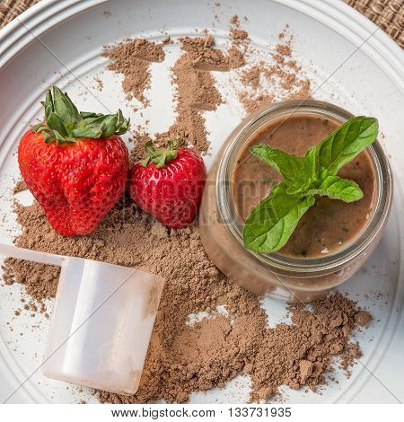 Meal replacement or protein shake in a jar from above.  Plate also has a scoop and fresh strawberries