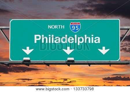 Interstate 95 south to Philadelphia highway sign with sunrise sky.