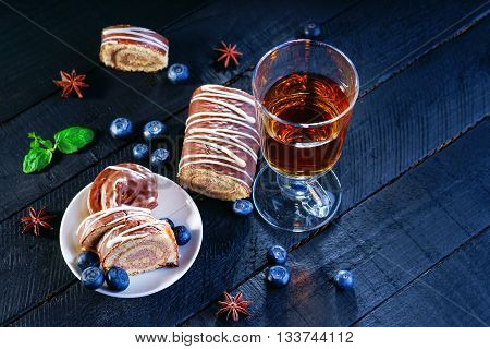 Slices of Swiss roll, blueberry and tea