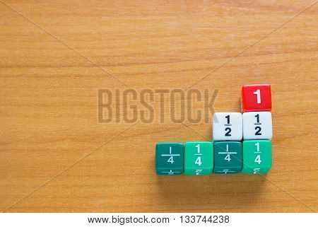 Color fraction dices; whole number half and quarters on wood table with room for copyspace