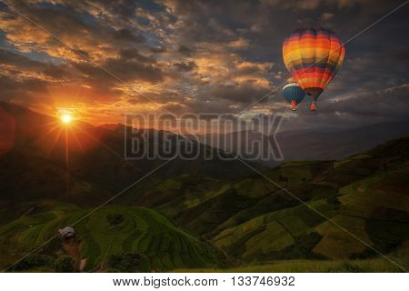 Hot air balloon over Rice fields on terraced in rainny season at Mu cang chai Vietnam. Rice fields prepare for transplant at Northwest Vietnam