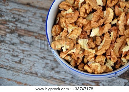 Walnuts. Walnut kernels. Clean organic walnuts. Nuts in the cup on vintage blue wooden background. Countryside agriculture. Walnut tree fresh fall harvest in the village.