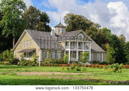 Manor house of P.A.Gannibal with a lawn and trees in the village Petrovskoye Pushkinskiye Gory Reserve Russia
