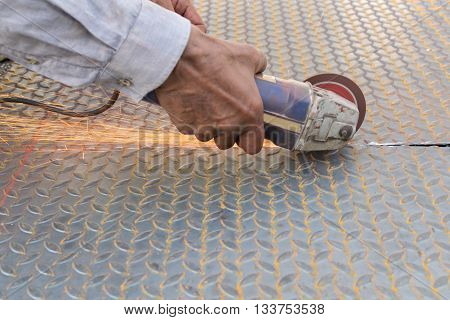 Worker Cutting A Metal
