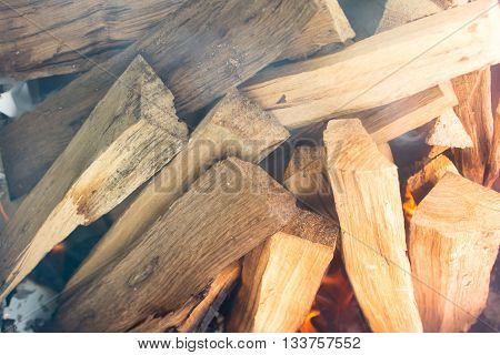 Closeup of logs smoking and burrning in preparation for nice barbecue