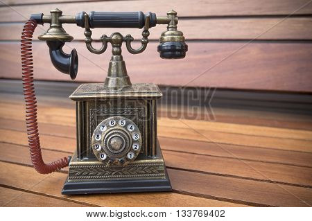 Retro Phone model vintage old dial Telephone on wood backgrond