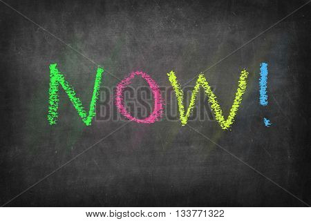 NOW colorful word on black blackboard background