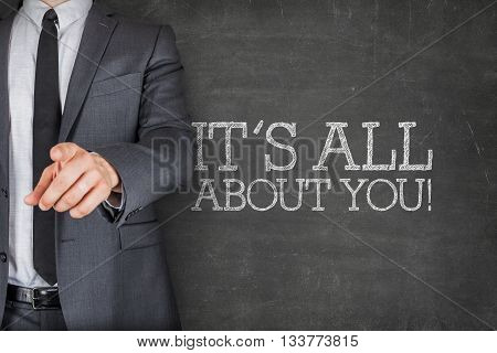 Its all about you on blackboard with businessman finger pointing