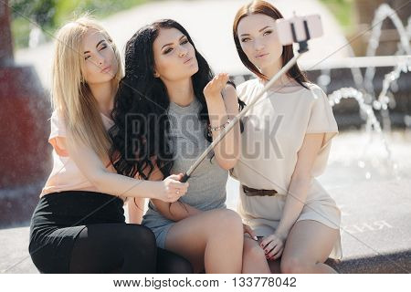 Three young girlfriend, brunette,blonde and girl with black long curly hair,nice smile,light makeup,wear jewelry,make selfi using monopod and smartphone,sitting together outdoors in the Park near the fountain in the summer
